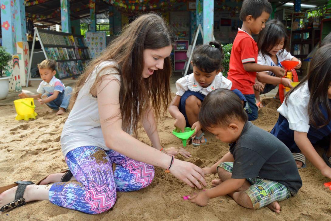 Joven voluntaria jugando con un niño.